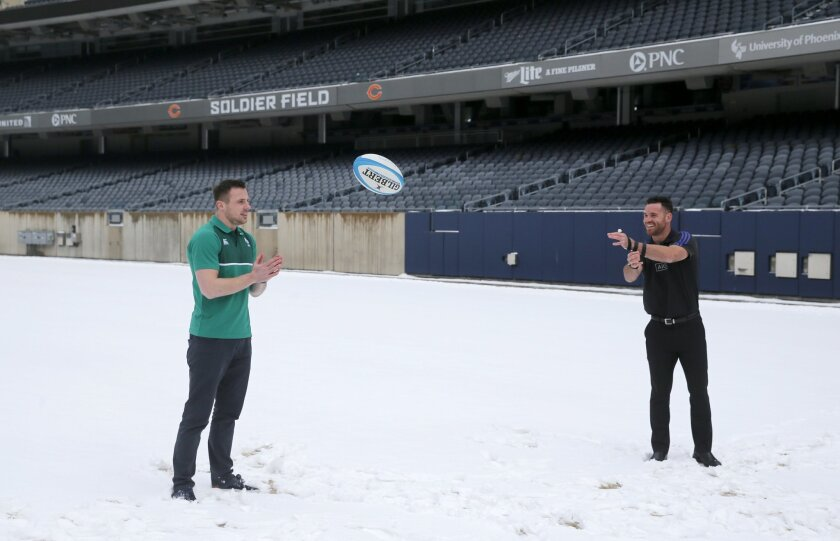 New Zealand All Blacks' Ryan Crotty, right, tosses a rugby football around with Ireland's Tommy Bowe, as they pose for photographers on the snow covered Soldier Field turf in Chicago, Tuesday, Feb. 16, 2016, after it was announced the teams will play there in November. (AP Photo/Charles Rex Arbogas