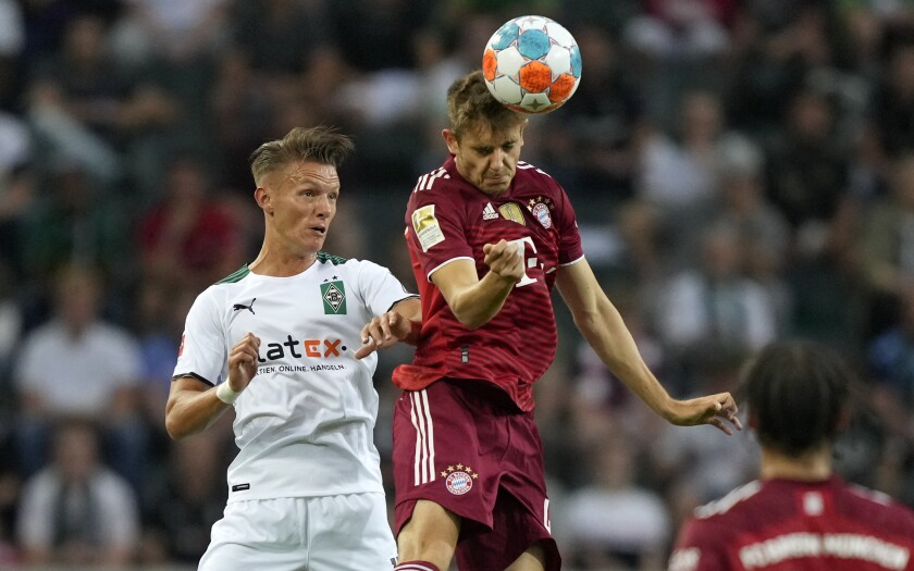 Bayern's Josip Stanisic, center, jumps for the ball during the German Bundesliga soccer match between Borussia Moenchengladbach and Bayern Munich in Moenchengladbach, Germany, Friday, Aug. 13, 2021. (AP Photo/Martin Meissner)