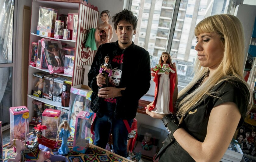 Artists Emiliano Paolini, left, and Marianela Perelli, pose for a photo while holding their Ken and Barbie doll,s respectively, dressed as religious figures, in Rosario, Argentina, Friday, Oct. 10, 2014. Paolini and Perelli had planed to exhibit 33 unique pieces of the fashion dolls on Saturday. The provocative art exhibit that features the dolls as religious figures such as the Virgin Mary and her boyfriend Ken as a crucified Jesus Christ has been canceled amid complaints and threats by angry believers, creators of the collection said Friday. (AP Photo/Marcelo Manera)