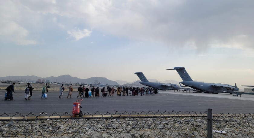 A line of evacuees on an airport tarmac near aircraft.