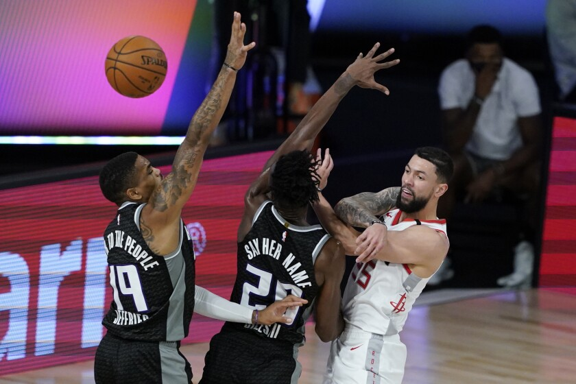 Houston Rockets' Austin Rivers (25) passes over Sacramento Kings' DaQuan Jeffries (19) and Harry Giles III (20) during the second half of an NBA basketball game Sunday, Aug. 9, 2020, in Lake Buena Vista, Fla. (AP Photo/Ashley Landis, Pool)