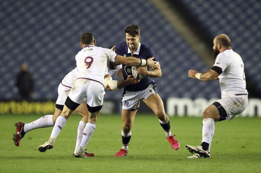 Scotland's Adam Hastings, center, is tackled by Georgia's Vasil Lobzhanidze battle for the ball during the Autumn International rugby match at BT Murrayfield Stadium, Edinburgh, Friday Oct. 23, 2020. (Jane Barlow/PA via AP)
