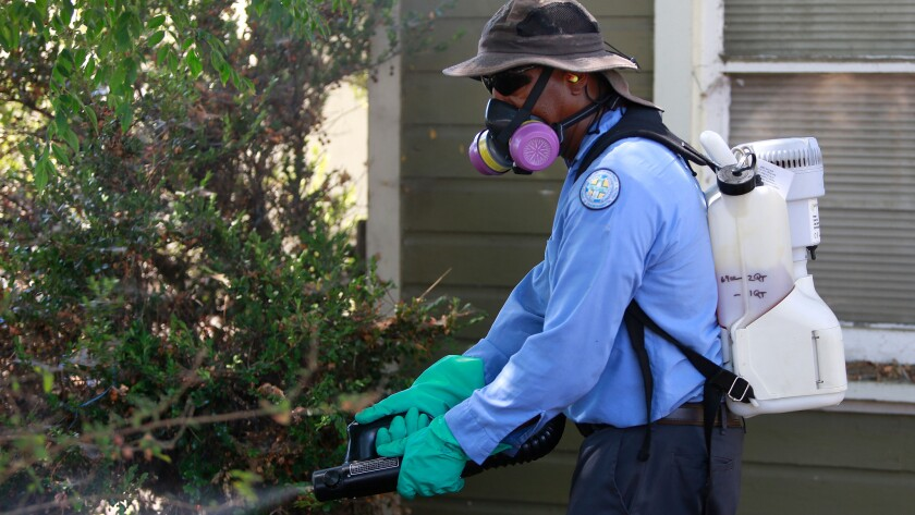 Sean Simmons, a vector control technician, sprays for the Zika virus at a home in the Mount Hope neighborhood of San Diego.