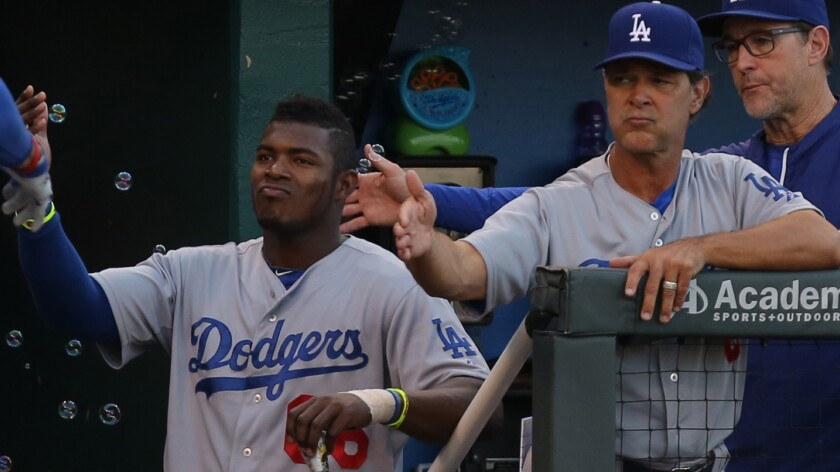 Dodgers right fielder Yasiel Puig and Manager Don Mattingly congratulate Matt Kemp (not pictured) on his home run against the Kansas City Royals on June 25.