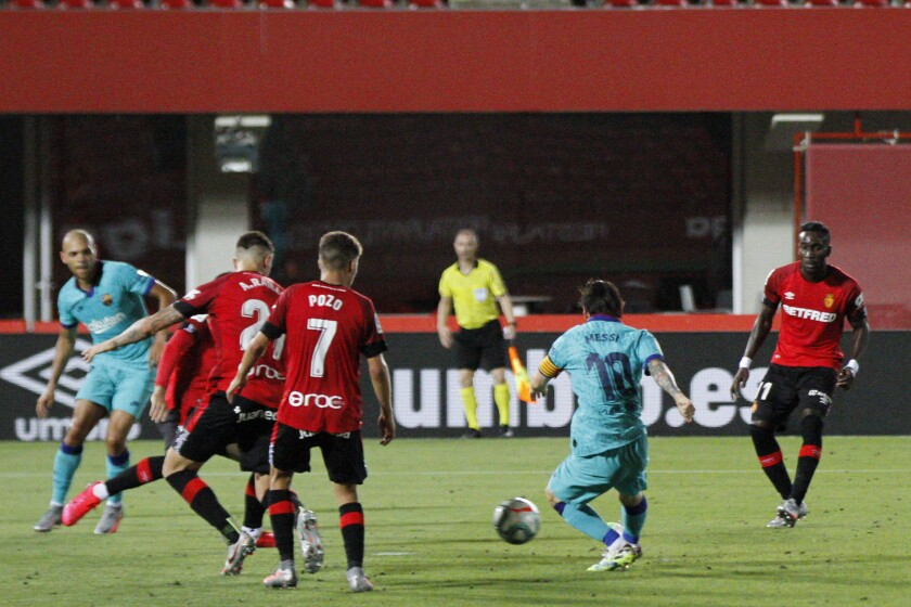 Barcelona's Lionel Messi, second right, kicks the ball to score his side's fourth goal during the Spanish La Liga soccer match between Mallorca and FC Barcelona at Son Moix Stadium in Palma de Mallorca, Spain, Saturday, June 13, 2020. With virtual crowds, daily matches and lots of testing for the coronavirus, soccer is coming back to Spain. The Spanish league resumes this week more than three months after it was suspended because of the COVID-19 pandemic. (AP Photo/Francisco Ubilla)