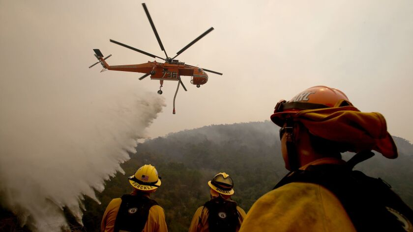 Firefighters watch as a helicopter drops water on the Alamo fire near Santa Maria on Saturday.