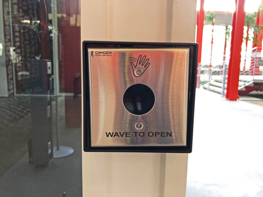 """A metal box bears the icon of a hand and says """"wave to open"""""""