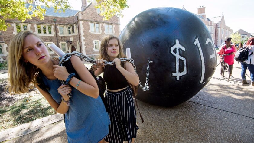 Students at Washington University in St. Louis pull a mock ball and chain representing the more than $1 trillion outstanding student debt.