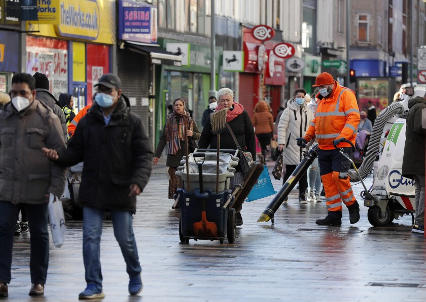 Road cleaners work in the town centre of Ilford in London, Friday, Jan. 29, 2021. In parts of east London, the pandemic is hitting much harder than most places in the U.K. The borough of Redbridge had the nation's second worst infection rate in January, with an estimated 1 in 15 residents thought to be infected. (AP Photo/Frank Augstein)