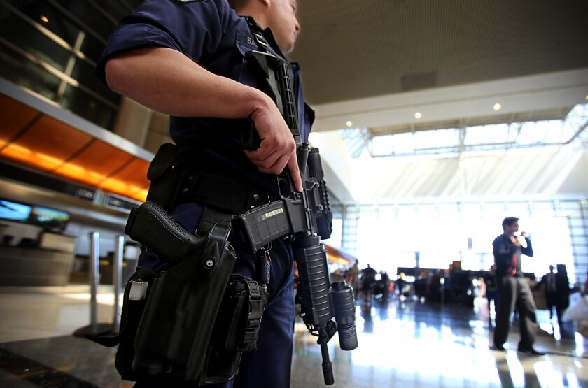 A heavily armed Los Angeles Airport Police Department officer stands guard at the Tom Bradley International Terminal at LAX. Months before a gunman's rampage le ft a TSA agent there dead, the department had changed its policy on the stationing of armed officers.