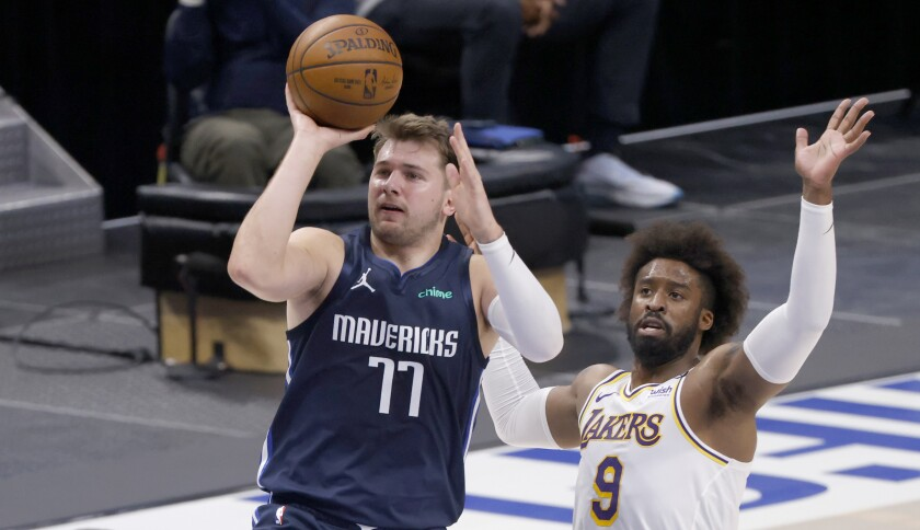 The Mavericks' Luka Doncic shoots as the Lakers' Wesley Matthews defends during the first half April 24, 2021.