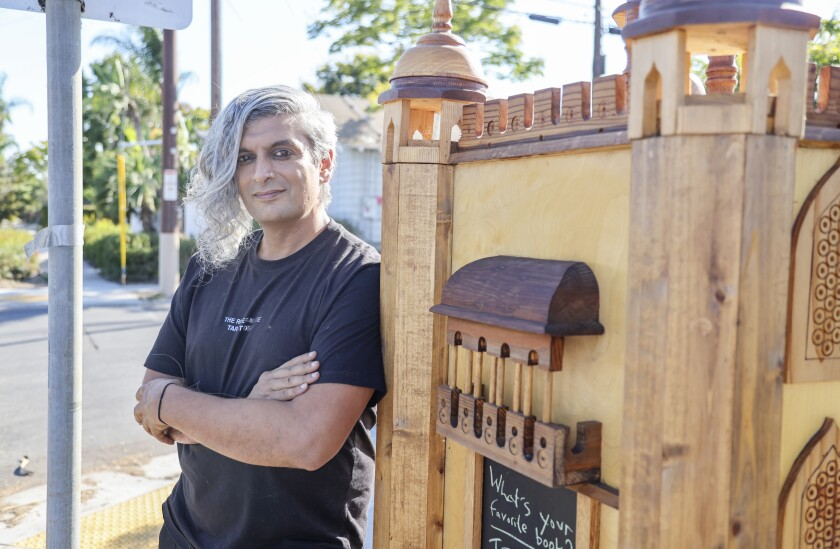 Kazim Ali photographed with a  Little Free Library in Normal Heights
