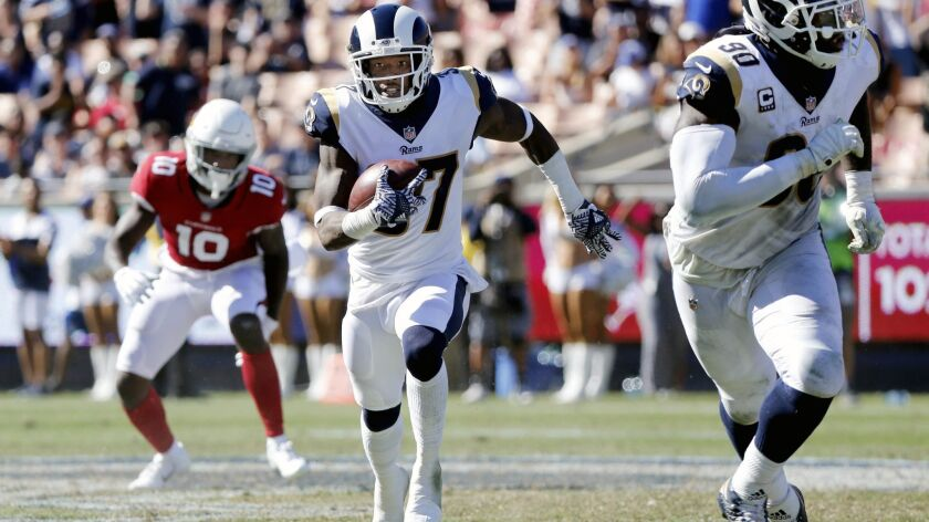 Rams defensive back Sam Shields, center, heads up filed after intercepting Arizona Cardinals quarterback Sam Bradford's pass in the second half at the Coliseum on Sept. 16.