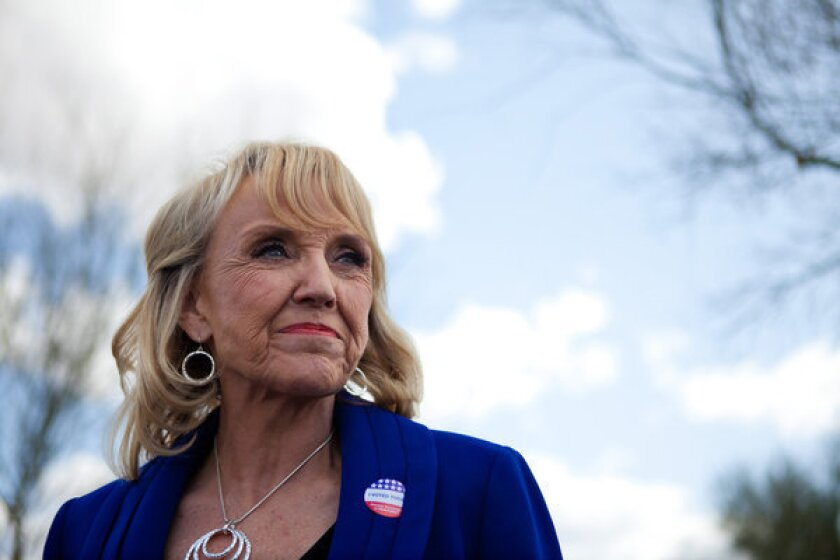Arizona Gov. Jan Brewer talks to the news media after voting in the Republican presidential primary.