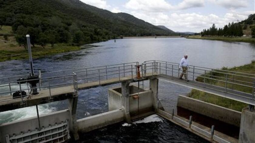 Experts will inspect the Moccasin Dam in Tuolumne County after a leak was reported on the dam face Thursday, officials said. Above, then-assistant general manager of San Francisco Public Utilities Commission Steven Ritchie walks over a reservoir bridge in 2014.