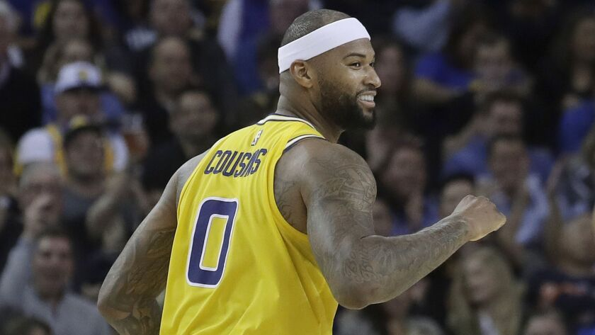 Golden State Warriors center DeMarcus Cousins smiles after scoring against the Denver Nuggets in 2019.
