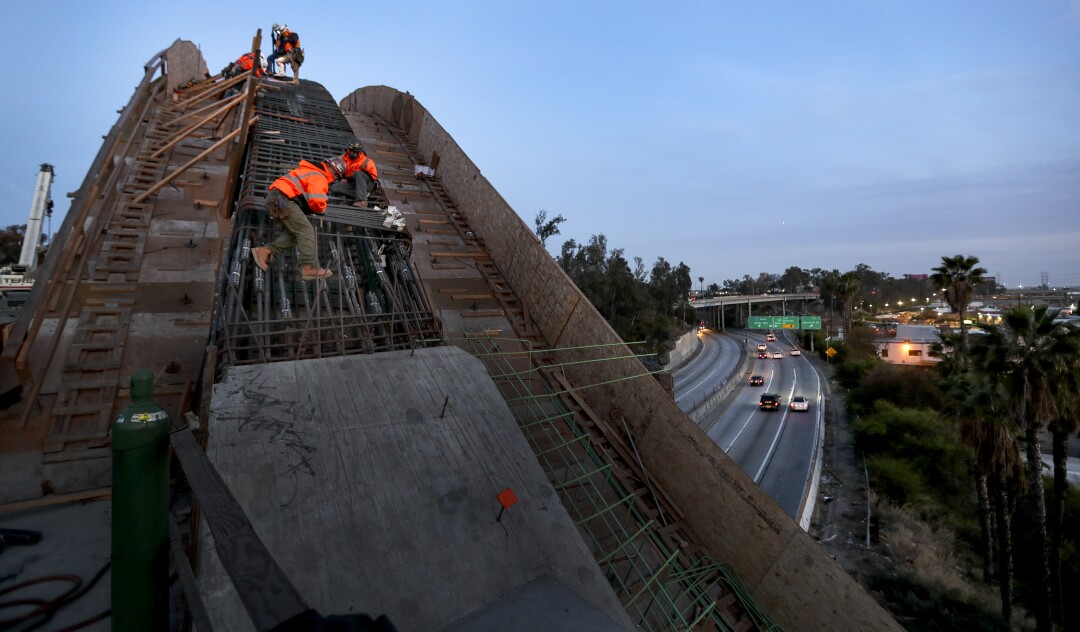 Traffic on the 101 Freeway whizzes by below as work continues on the new bridge