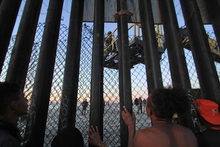Migrantes de la primera caravana, que salió desde honduras y recorrió el territorio mexicano, comienzan a congregarse en la valla fronteriza de Tijuana (México). EFE
