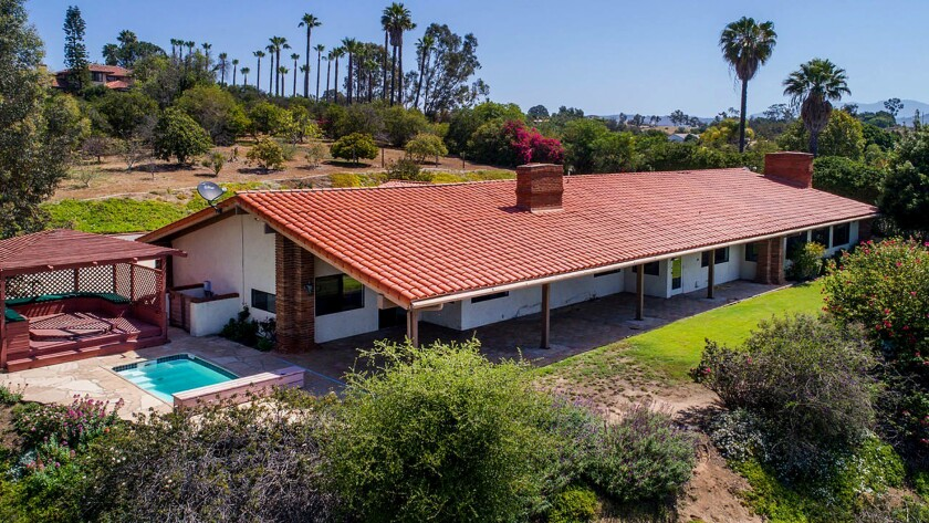 FALLBROOK: This gated hacienda features heavy doses of wood and opens to a patio with a gazebo, spa