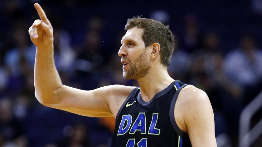 Dallas Mavericks forward Dirk Nowitzki waves to the Phoenix Suns bench prior to an NBA basketball ga