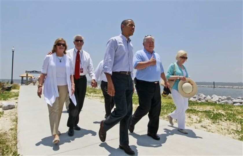 President Barack Obama walks with Mississippi Gov. Haley Barbour, second from right, and Gulfport Mayor George Schloegel, second from left, after meeting with residents affected by the BP Deepwater Horizon oil spill, Monday, June 14, 2010, in Gulfport, Miss. Peggy Schloegel, the mayor's wife is at