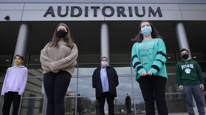 """While wearing protective masks due to the COVID-19 outbreak, Jim Howard, a drama teacher at Westwood, Mass., High School, center, poses with his student actors outside the school's auditorium after working on their virtual performance of Shakespeare's """"Romeo and Juliet,"""" Monday, Nov. 16, 2020, in Westwood. The production, which would usually be presented onstage, shifted to a virtual audience due to the pandemic. From left are Ryan Kaplan, who portrays the friar, Lucy Vitali, who portrays Juliet, Howard, Cassidy Hall, who portrays the nurse, and Alex Mansour, who portrays Romeo. (AP Photo/Charles Krupa)"""