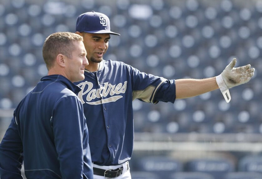 San Diego Padres starting pitcher Tyson Ross, right, talks with Padres general manager Josh Byrnes during activities prior to a baseball game against the Pittsburgh Pirates Monday, June 2, 2014, in San Diego. (AP Photo/Lenny Ignelzi)