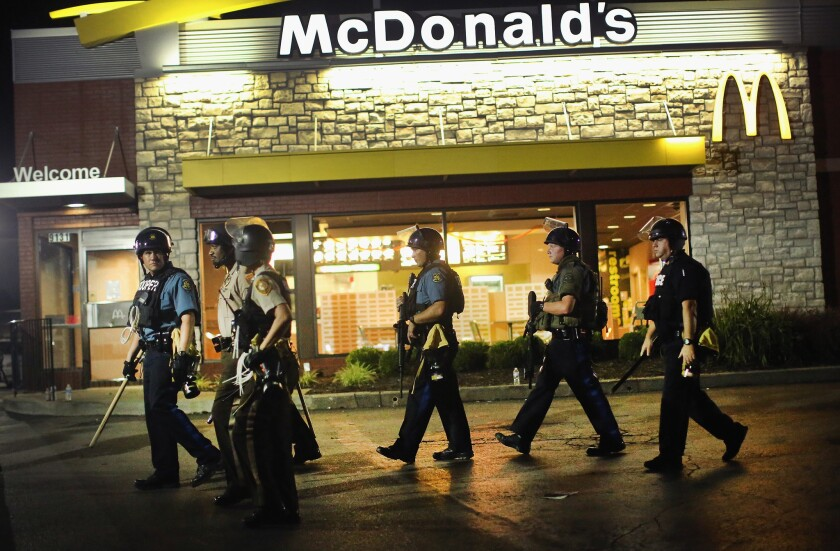 The unrest in Ferguson inspires a design analysis of American commercial strips. In this image, taken Tuesday evening, police watch demonstrators outside a McDonald's.