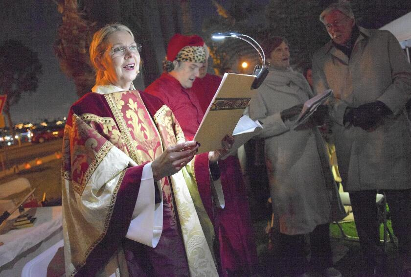 The Rev. Canon Cindy Evans Voorhees leads St. James the Great Episcopal Church members in an outdoor Christmas Eve celebration last year at Lido Park in Newport Beach. Church members have held services in various locations since losing access to the church's Via Lido property earlier in 2015.