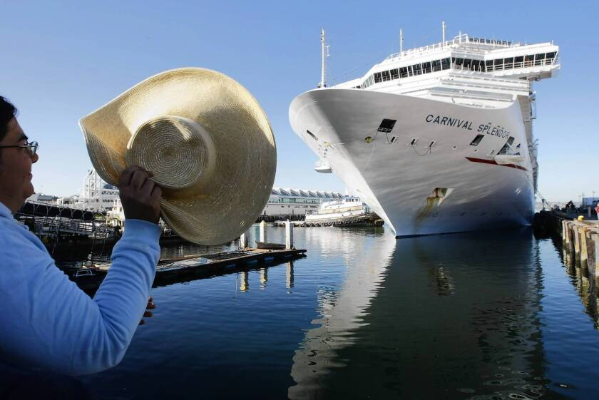 A spectator watches as a tug nudges the Carnival Splendor into the San Diego Cruise Ship Terminal. The ship and its nearly 4,500 passengers and crew were towed into port after a fire. Many air conditioners, refrigerators and toilets stopped working during the four-day tow.