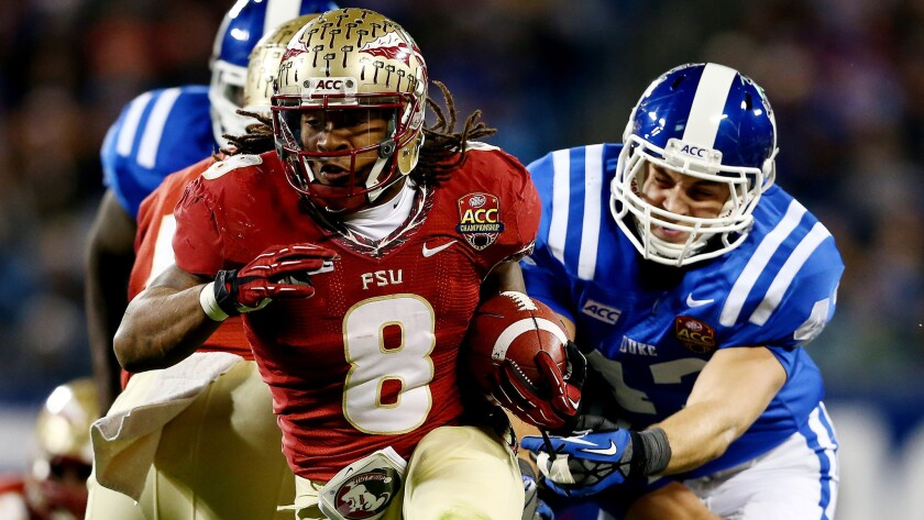 Florida State's Devonta Freeman carries the ball during the Seminoles' win in the Atlantic Coast Conference championship game over Duke in December. The ACC will continue to have an eight-game conference schedule in 2014.
