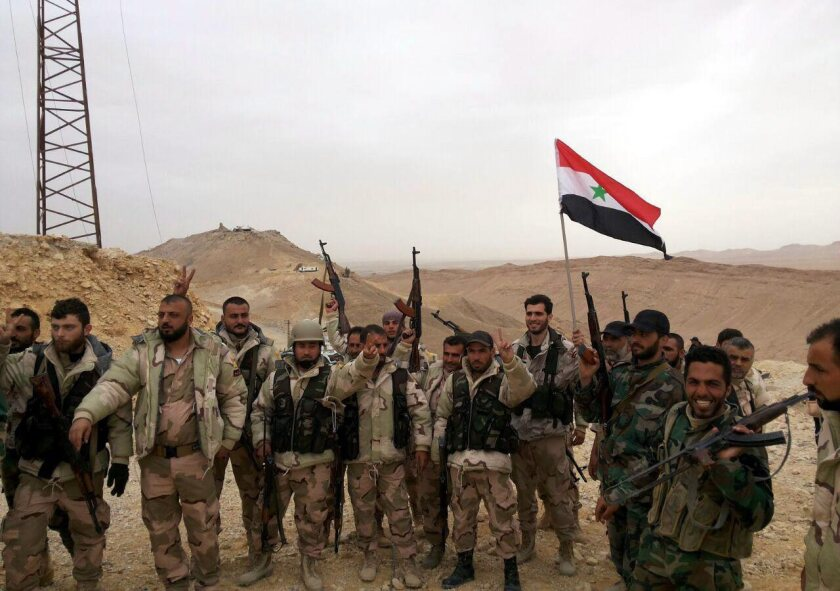 Syrian soldiers display the national flag during an operation in Palmyra.