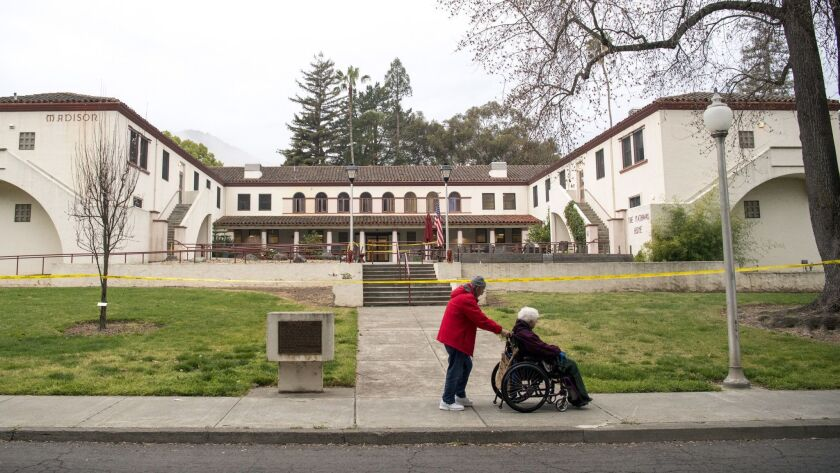 A man pushes a woman in a wheelchair past the Veterans Home of California in Yountville in 2018.