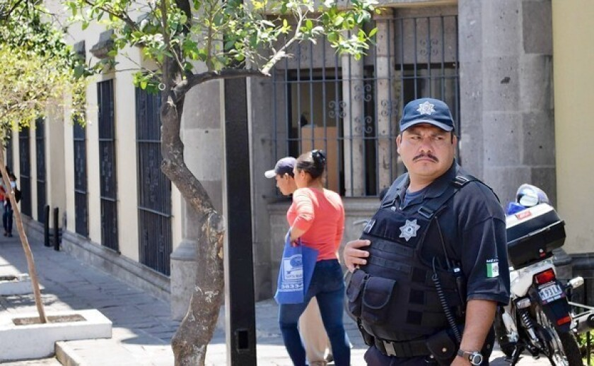 A police officer patrols in downtown Zapopan, outside Guadalajara, Mexico. The mayor's office there recently learned that of the roughly 1,600 police officers who had taken a trustworthiness test, 389 had failed.