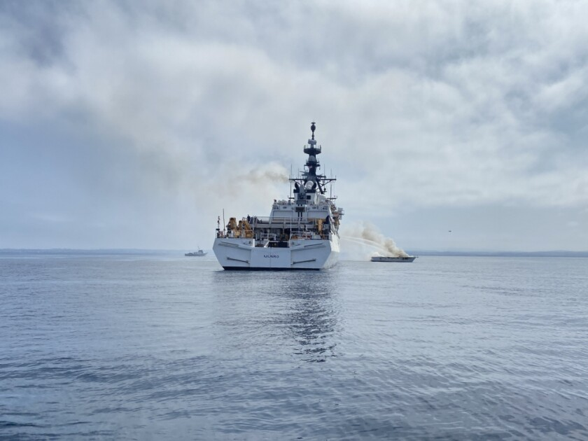 Coast Guard cutter dousing smaller boat with water