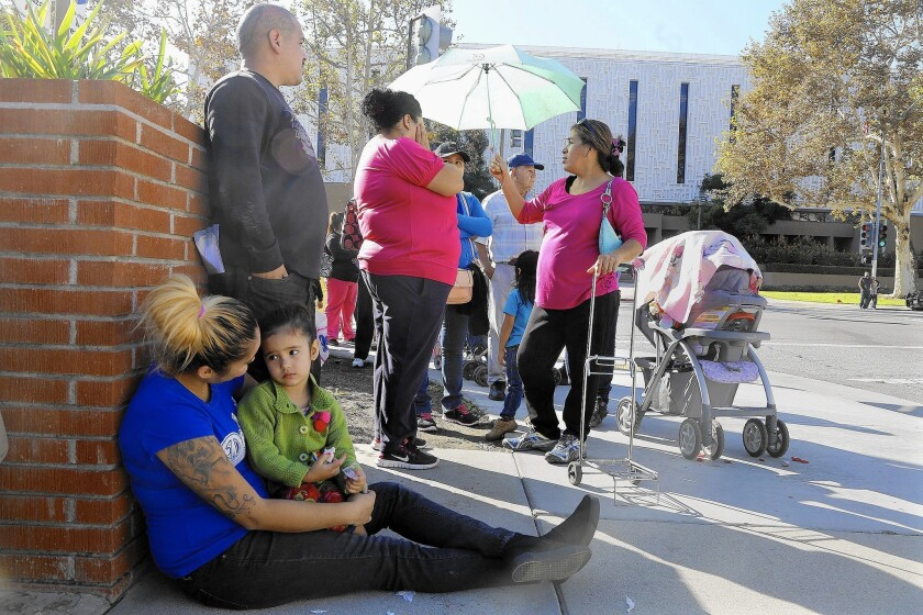 Needy families wait to sign up to receive a Christmas food basket and toys as part of the El Monte Police Department's annual holiday giveaway. In the densely populated city of 113,000, nearly a quarter of the population lives below the poverty line.