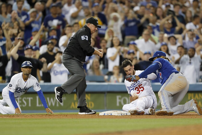 Cody Bellinger is tagged out by Toronto's Vladimir Guerrero Jr. after trying to stretch a triple out of a three-run double in the fourth inning Tuesday night at Dodger Stadium.