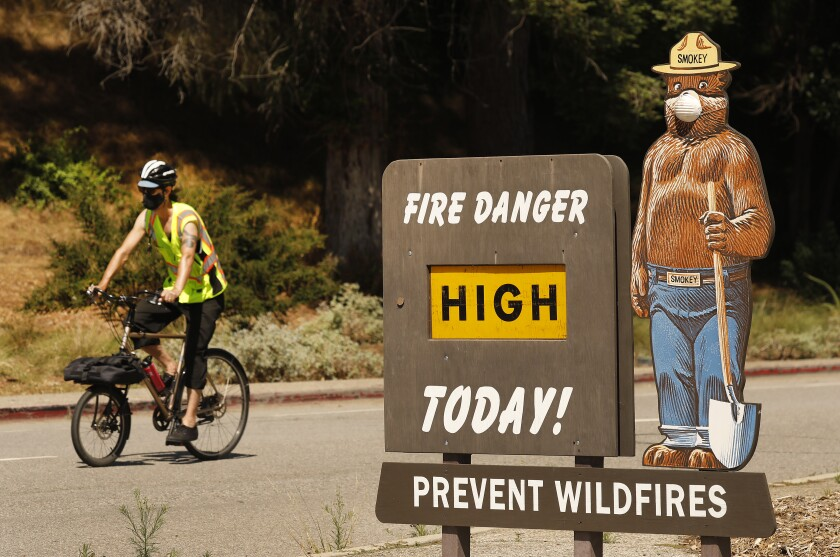 Smokey Bear wears a mask as a sign warns of High Fire Danger at the Riverside Drive and Los Feliz Boulevard entrance to Griffith Park on Tuesday.