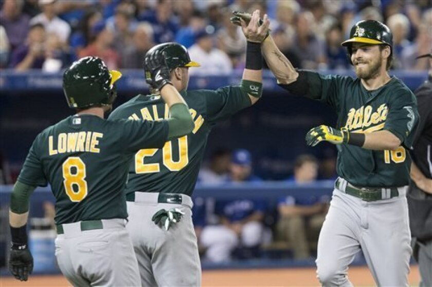 Oakland Athletics' Josh Reddick, right, celebrates at the plate with Josh Donaldson, center, and Jed Lowrie after hitting a three-run home run off Toronto Blue Jays pitcher Juan Perez during the sixth inning of a baseball game in Toronto on Friday, Aug. 9, 2013. (AP Photo/The Canadian Press, Chris Young)