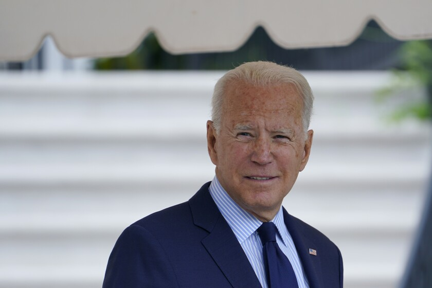 President Biden in a suit in front of white stairs