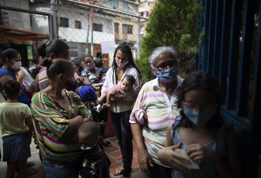 Varias mujeres y niños, con mascarillas para protegerse del coronavirus,