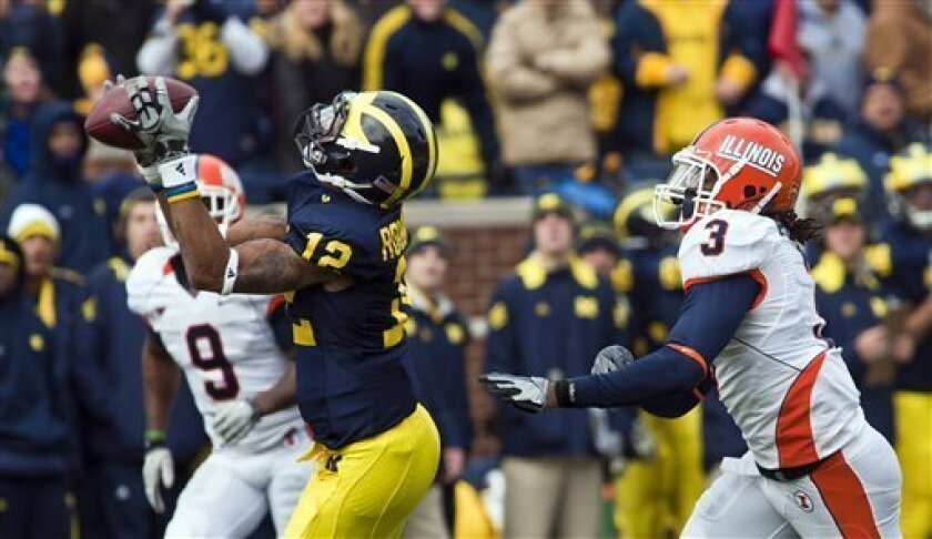 Michigan slot receiver Roy Roundtree (12) beats Illinois cornerback Tavon Wilson (3) for a 75-yard catch in the second quarter of an NCAA college football game, Saturday, Nov. 6, 2010, in Ann Arbor, Mich. (AP Photo/Tony Ding)
