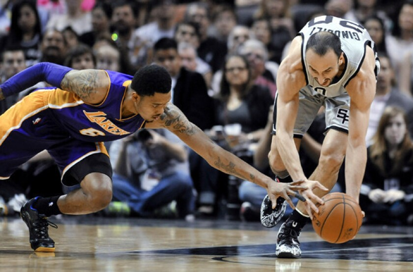 Spurs guard Manu Ginobili gets to a loose ball before Lakers guard Kent Bazemore in the first half Friday night in San Antonio.