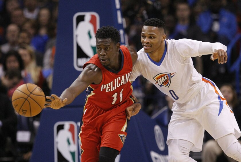 New Orleans Pelicans guard Jrue Holiday (11) reaches for the ball in front of Oklahoma City Thunder guard Russell Westbrook (0) in the second quarter of an NBA basketball game in Oklahoma City, Thursday, Feb. 11, 2016. (AP Photo/Sue Ogrocki)