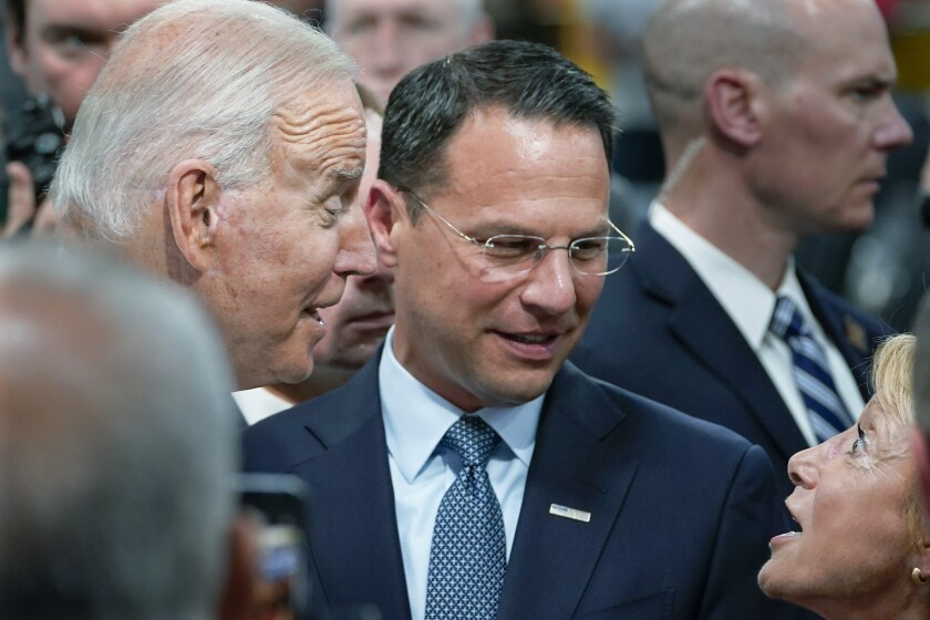 FILE— In this July 28, 2021 file photo Pennsylvania Attorney General Josh Shapiro, center, and President Joe Biden talk with people at the Lehigh Valley operations facility for Mack Trucks in Macungie, Pa. The high-profile attorney general will formally announce his candidacy for governor of Pennsylvania on Wednesday, Oct. 13, 2021, entering the 2022 race. (AP Photo/Susan Walsh, File)