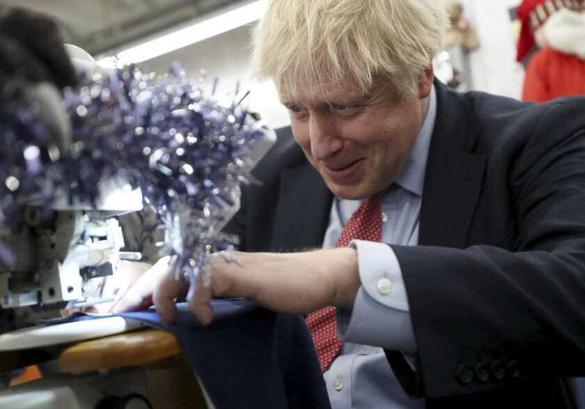 Britain's Prime Minister Boris Johnson tries to operate a sewing machine decorated for Christmas, during an election campaign stop at John Smedley Mill in Matlock, England, Thursday Dec. 5, 2019. The UK goes to the polls in a General Election on Dec. 12. (Hannah McKay/Pool via AP)
