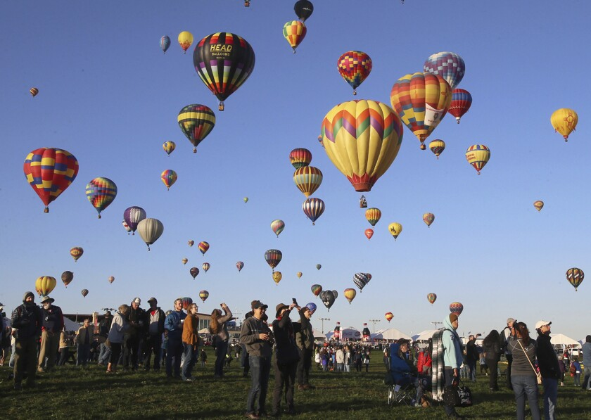 Spectators watch hot air balloons liftoff at the Albuquerque International Balloon Fiesta in Albuquerque, N.M., Sunday, Oct. 6, 2019. (Jerry Larson/Waco Tribune-Herald via AP)