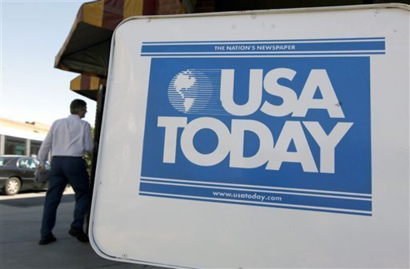 FILE - In this Sept. 29, 2009 file photo, a USA Today newspaper box is shown outside a restaurant in Charlotte, N.C. Gannett Co., the largest U.S. newspaper publisher, said Monday, Feb. 1, 2010, it turned a profit in the fourth quarter, helped by a drop in one-time costs and a smaller ad decline.(AP Photo/Chuck Burton, File)