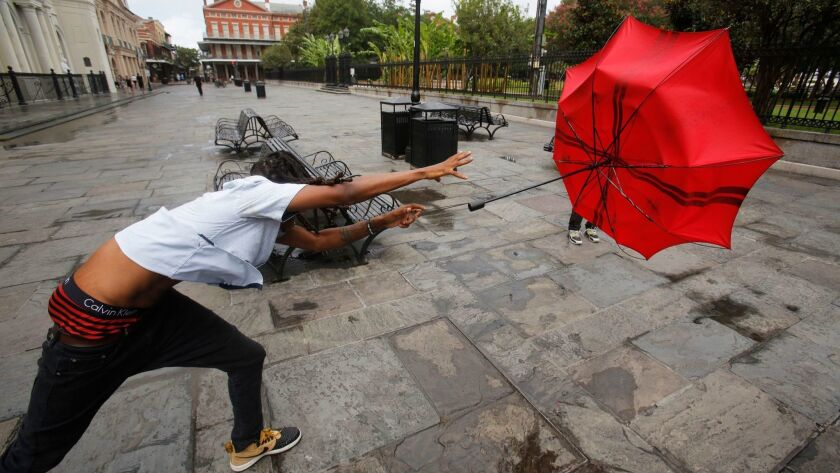 A man in the French Quarter plays with his umbrella in the wind of the storm Barry in New Orleans, on Friday.