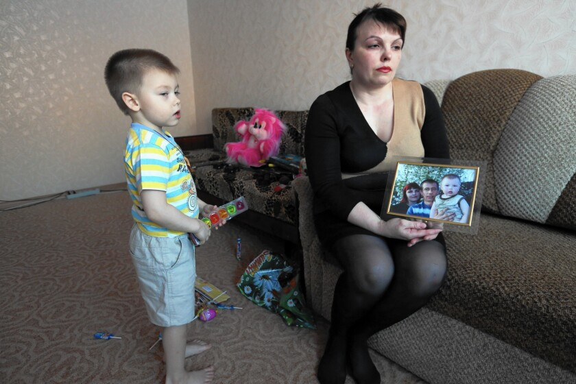 Natalya Zhitineva and her son, Denis, with a photo of them together with Natalya's husband, Alexander Zhitinev, who went to fight in Ukraine.